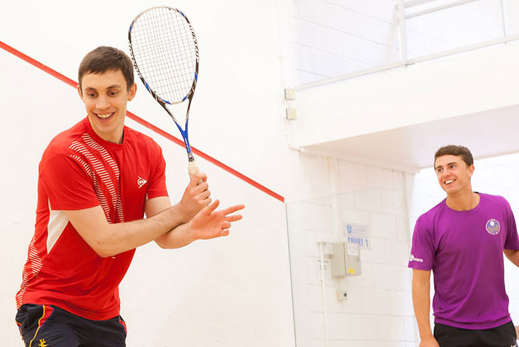 Two adult squash players enjoying themselves on court